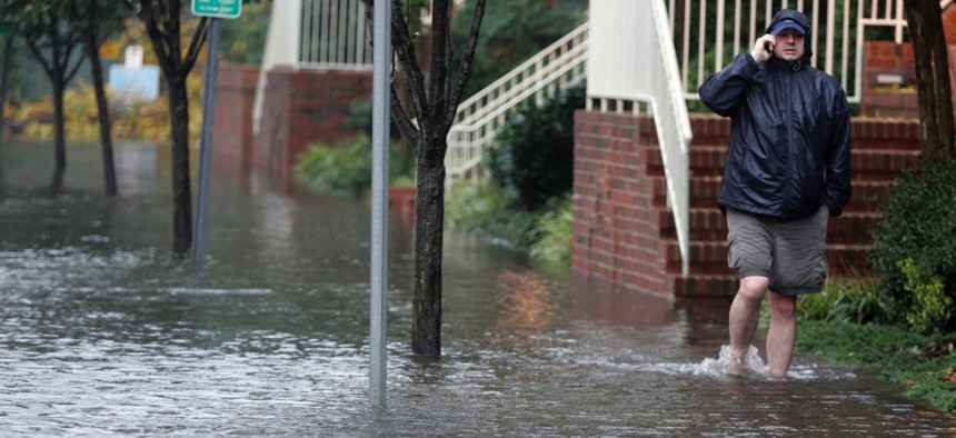 A resident talks on his cell as he walks through a flooded street in Norfolk, Va., on Nov. 13, 2009, as the area was hit by remnants of Tropical Storm Ida.