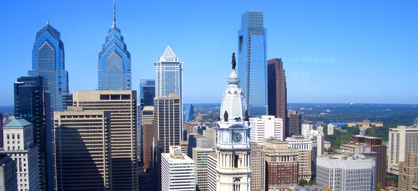 Comcast Center's tower, center right, rises behind the historic clocktower of Philadelphia City Hall.