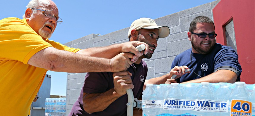 Leo Block, left, Matari Phason, center, and Brian Juarez, right, push part of a shipment of 20,000 water bottles donated by Yellow Cab of Phoenix to Central Arizona Shelter Services, Arizona's largest homeless shelter.