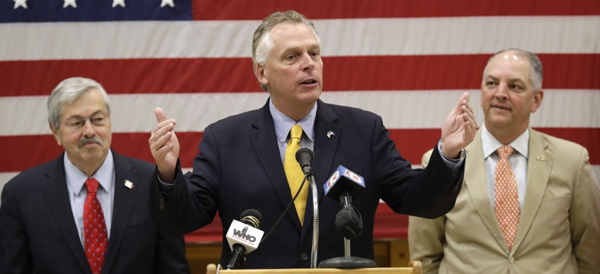 Virginia Gov. Terry McAuliffe, center, speaks during a news conference as Iowa Gov. Terry Branstad, left, and Louisiana Gov. John Bel Edwards, right, look on, Friday, July 15, 2016, at EFCO Corp. in Des Moines, Iowa.
