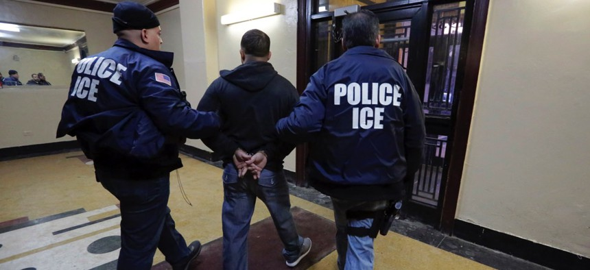 Immigration & Customs Enforcement officers escort an arrestee in a New York City apartment building during a series of early-morning raids in 2015.