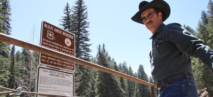 In this May 15, 2014, file photo, Otero cattle rancher association president Gary Stone inspects a newly posted warning sign in Weed, New Mexico. The forest service had closed off areas to prevent damage to New Mexico meadow jumping mouse's habit.