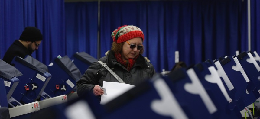 Chicago resident Sonja Russell walks up to a voting machine to cast her ballot in Illinois primary elections at the city's new early voting super site downtown on March 13.
