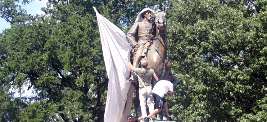Protesters attempt to drape Nathan Bedford Forrest statue in a canvas calling for its removal in the #TakeEmDown901 campaign to dismantle confederate propaganda, August 19, 2017.