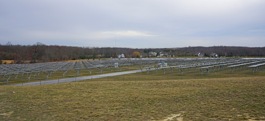View of a large solar energy farm with solar panels lined up in a field in New Jersey.