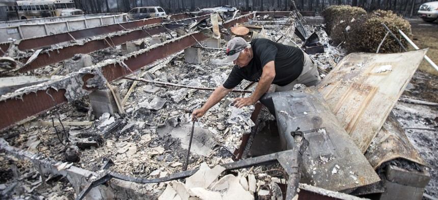 Mike Thornburg tries to salvage items from his mother's home after wildfires ravaged the neighborhood in Eastpoint, Fla.