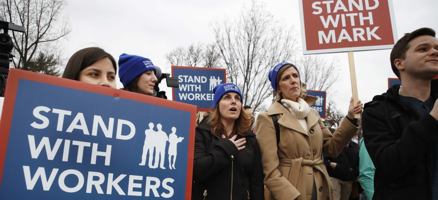 Danica Alink, of McLean, Va., center, and Beth Feeley, of Wilmette, Illi., right, say the Pledge of Allegiance at the start of a rally supporting Mark Janus, outside of the Supreme Court, Monday, Feb. 26, 2018, in Washington.