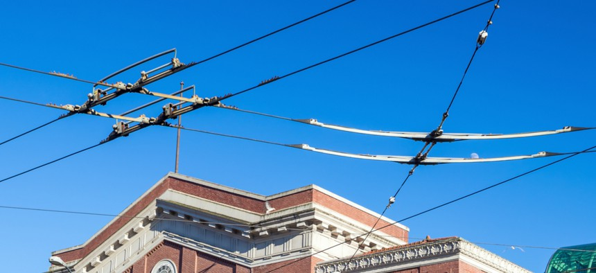 Trolleybus wires are suspended above the intersection of Fourth Avenue South and Jackson Street in front of Seattle's former Union Station.