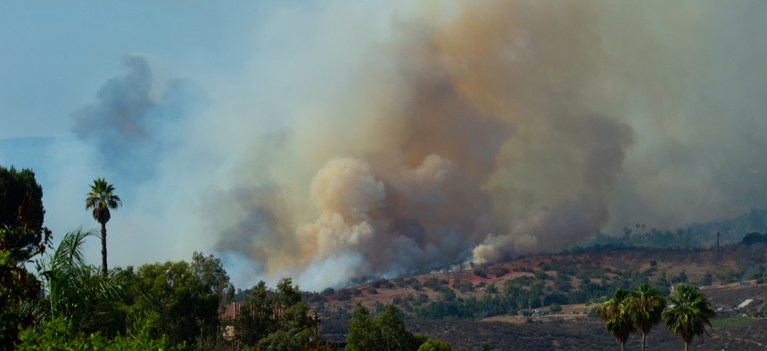 CalFire on July 29, 2018 battles wildfire as smoke rises near Fallbrook, California in San Diego County.