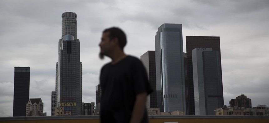 Homeless James Hernandez, a 27-year-old Houston, Texas native, looks away while watching his two daughters play on the rooftop of the Union Rescue Mission as the skyline of downtown Los Angeles is visible in the background, in May 2016.