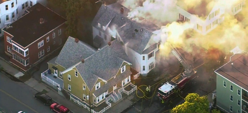 firefighters battle a large structure fire in Lawrence, Mass. on Thursday.