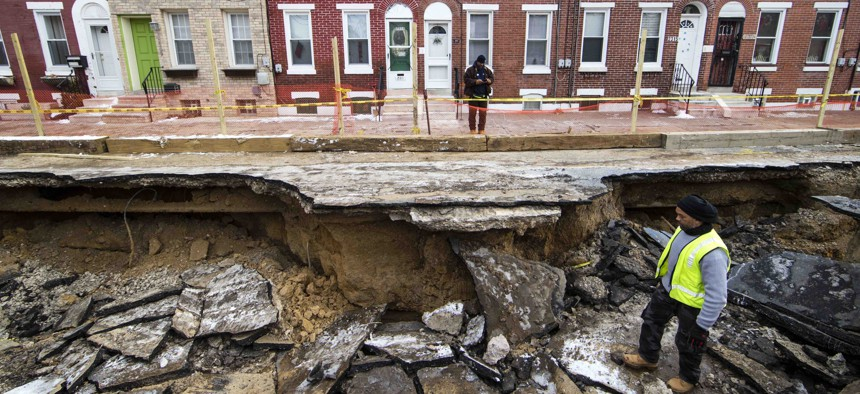 Workers inspect a sinkhole in Philadelphia, Monday, Jan. 9, 2017. The Philadelphia Water Department said a water main break caused the sinkhole to open up on the street.