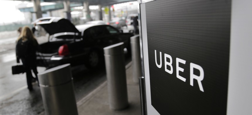 In this March 15, 2017 file photo, a sign marks a pick-up point for the Uber car service at LaGuardia Airport in New York.