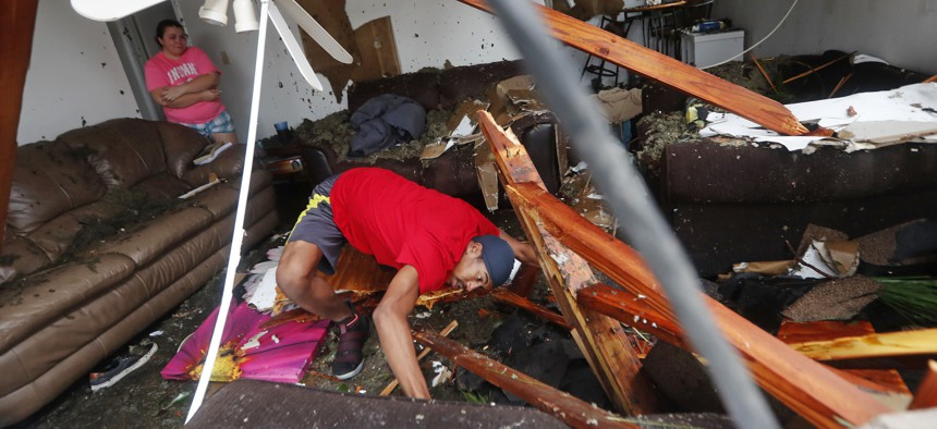 Dorian Carter looks under furniture for a missing cat after several trees fell on their home during Hurricane Michael in Panama City, Fla., Wednesday, Oct. 10, 2018.