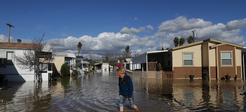 A man walks down a flooded street in South Bay Mobile Home Park in San Jose, Calif. on Feb. 22, 2017.
