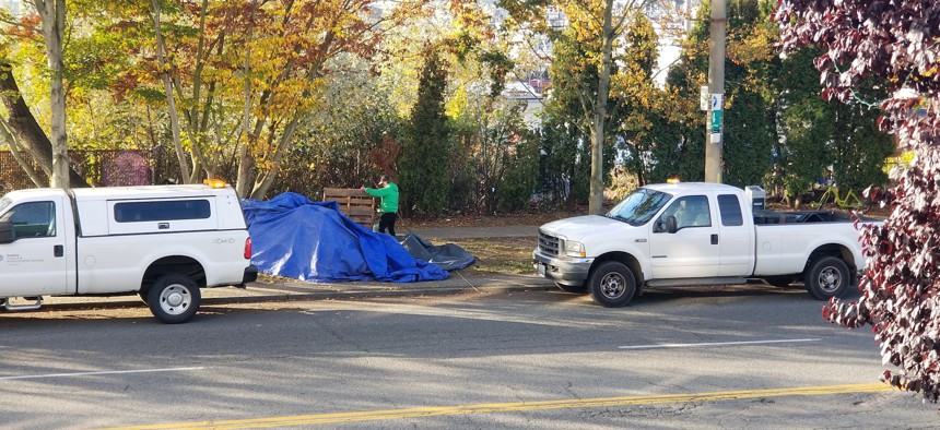 A city work crew in Seattle clears a homeless camp along NW Market Street in the Ballard neighborhood on Thursday morning.