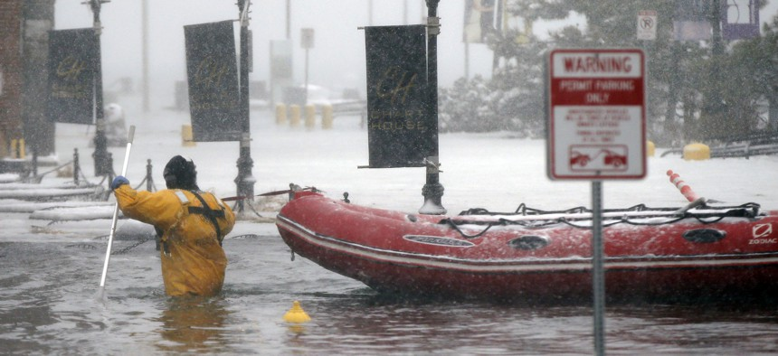 In this Jan. 4, 2018 file photo, a Boston firefighter wades through waters from Boston Harbor that flooded onto Long Wharf in Boston.
