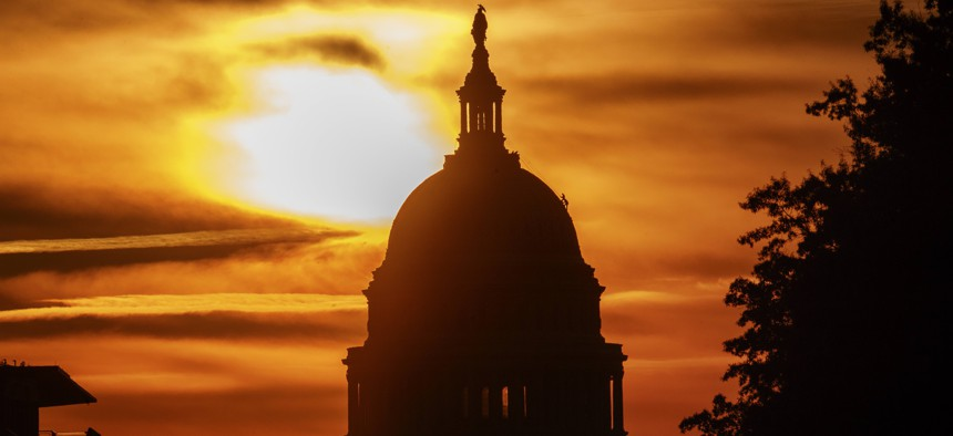 The rising sun silhouettes the U.S. Capitol dome at daybreak, Friday, Oct. 26, 2018, in Washington.