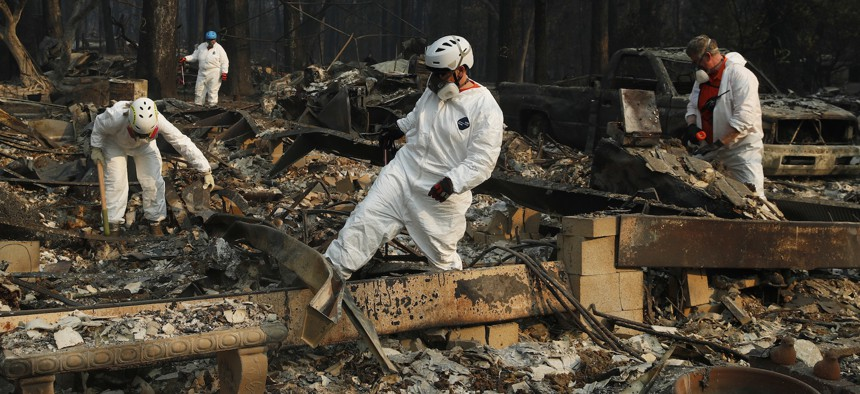 Search and rescue personnel search a home for human remains in the aftermath of the Camp fire in Paradise, Calif. on Friday.