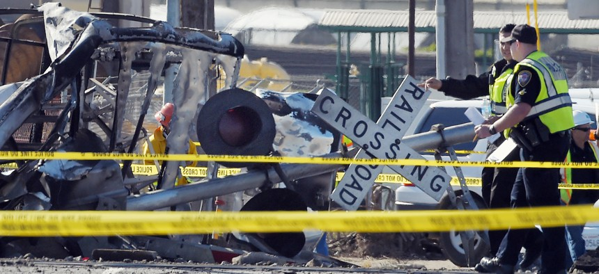 In this Tuesday, Feb. 24, 2015, file photo, police officers stand near a Metrolink train that hit a truck, left, and then derailed at a railroad crossing in Oxnard, Calif.