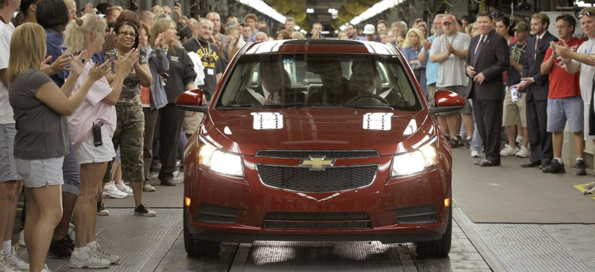 In this file photo taken Sept. 8, 2010, General Motors workers cheer as the first Chevrolet Cruze compact sedan off the assembly line, at the GM factory in Lordstown, Ohio.
