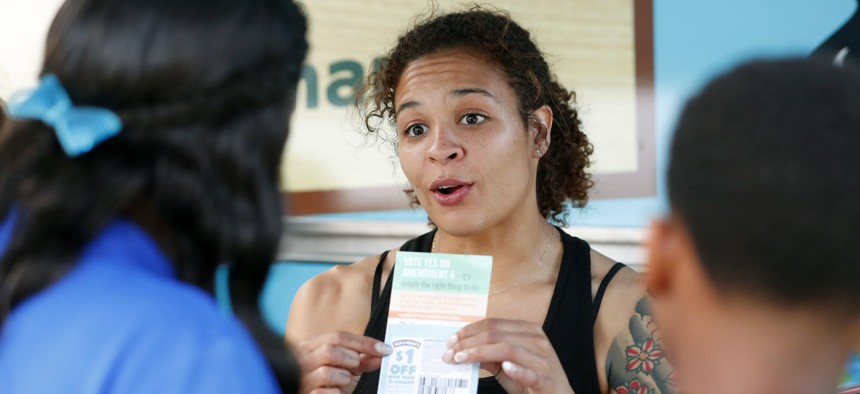 """In this, Monday, Oct. 22, 2018 photo, Jessica Jones, center, speaks to people gathered around the Ben & Jerry's """"Yes on 4"""" Truck about Amendment 4, which asks voters to restore the voting rights of people with past felony convictions."""