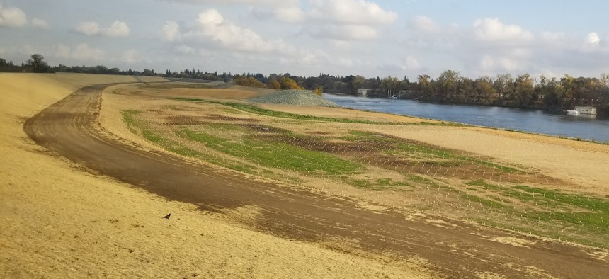 A newly constructed set back levee, at left, in West Sacramento, California was constructed with gaps to allow floodwaters from the Sacramento River to flood the space between the new levee and the old one, at center..