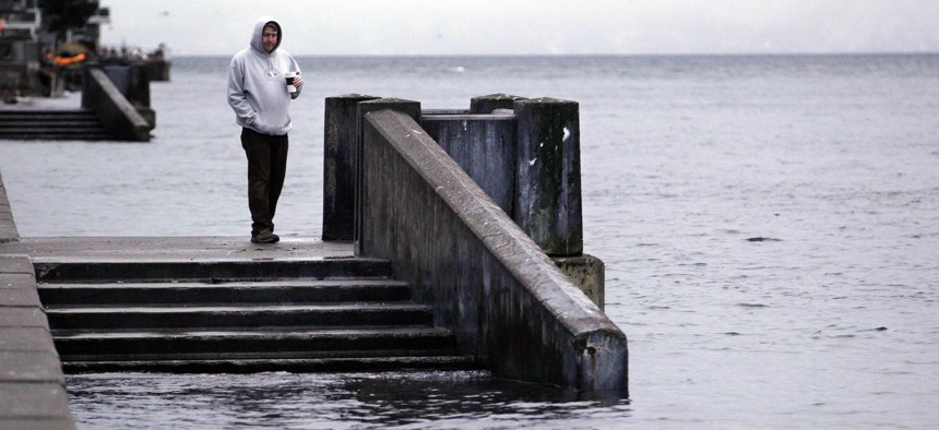 """A pedestrian looks at stairs leading to water during the peak of a """"king tide"""" Tuesday morning, Dec. 27, 2011, along Alki Beach in Seattle"""