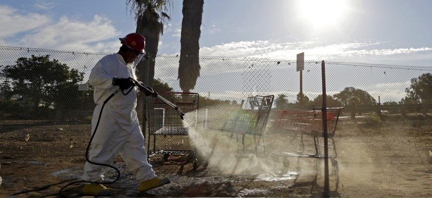 In this Sept. 25, 2017 photo, a worker sprays a bleach solution on a sidewalk in downtown San Diego as part of an effort to control a deadly hepatitis A outbreak.
