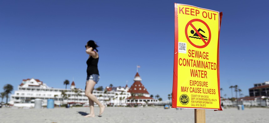 A sign warns of sewage contaminated ocean waters on a beach in front of the iconic Hotel del Coronado on Wednesday, March 1, 2017, in Coronado, Calif.