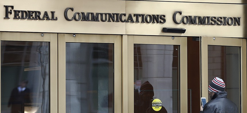 A person with a smart phone enters the Federal Communications Commission (FCC) in Washington on Dec. 14, 2017.