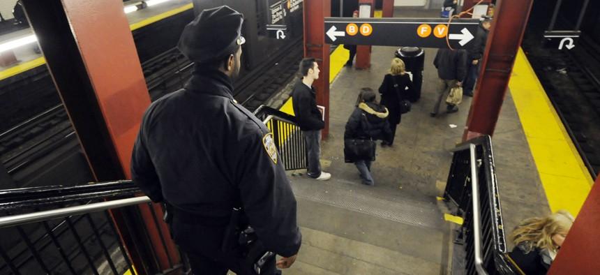 A New York police officer walks down stairs toward a subway platform, in midtown Manhattan.