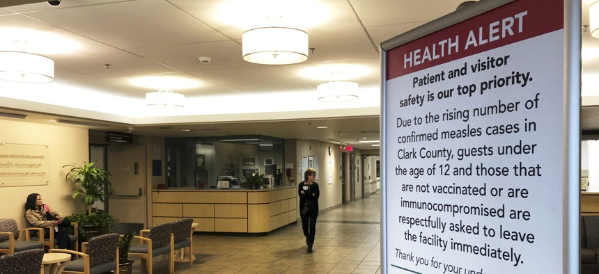 In this Jan. 25, 2019 file photo, a sign prohibiting all children under 12 and unvaccinated adults stands at the entrance to PeaceHealth Southwest Medical Center in Vancouver, Wash.