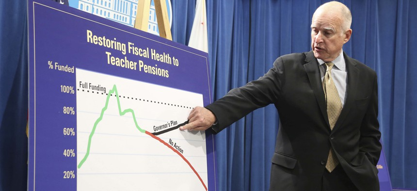 Former California governor, Jerry Brown, points to a chart showing his plan to fund teacher pensions in May of 2014.