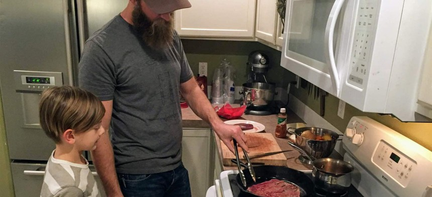 Nate Lindskoog and his son Jett, 8, cook venison tacos in their Nampa, Idaho, home. The deer was killed by a car a year earlier.