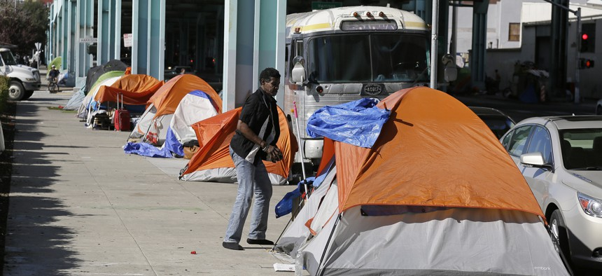 In this Feb. 23, 2016 file photo, a man stands outside his tent on Division Street in San Francisco.
