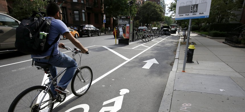 A cyclist in 2016 enters a bike lane that is routed between parked cars and the sidewalk in Boston.