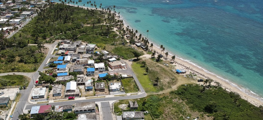 This June 2018 photo shows an aerial view of the Viequez neighborhood, east of San Juan, Puerto Rico.  Nine months after Hurricane Maria, blue plastic tarps still protected thousands of homes.