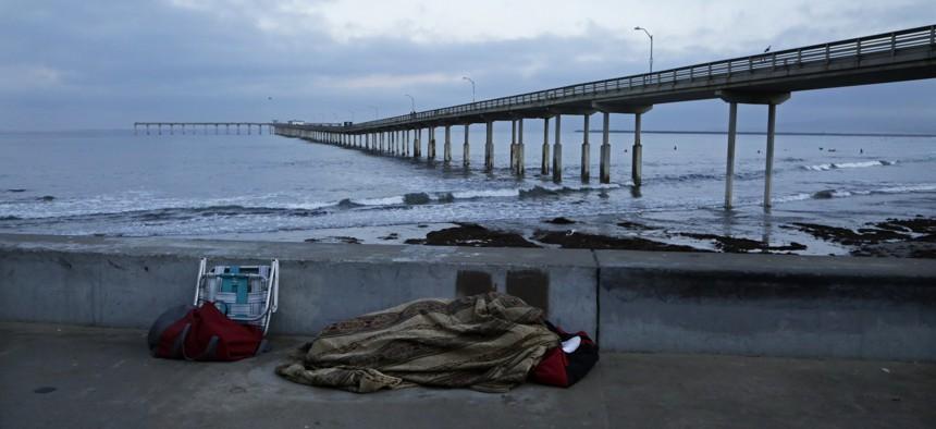A homeless person sleeps on a beach near the Ocean Beach Pier in San Diego.
