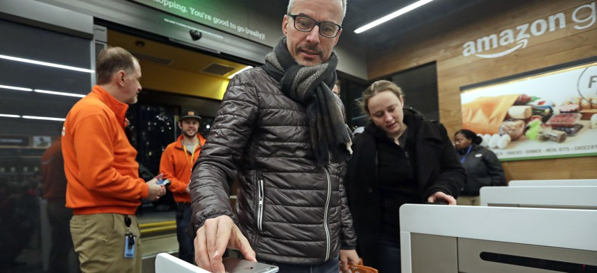 A customer scans his phone app at the entrance to an Amazon Go store in Seattle.