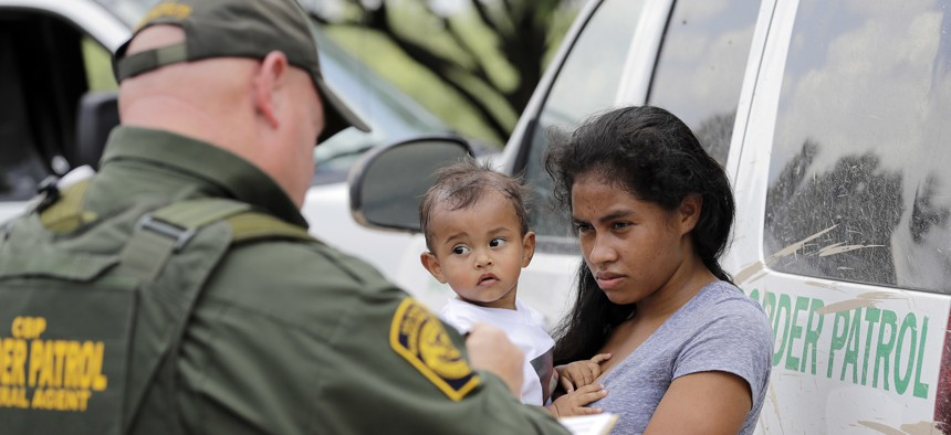A mother migrating from Honduras holds her 1-year-old child last year while surrendering to U.S. Border Patrol agents after crossing the border near McAllen, Texas.