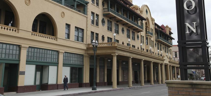 A man walks past the historic Hotel Stockton in Stockton, Calif.