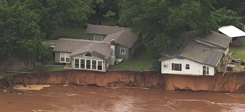This image taken from video provided by KOCO-5 shows homes dangerously close to the Cimarron River on May 22, 2019 near Crescent, Oka.