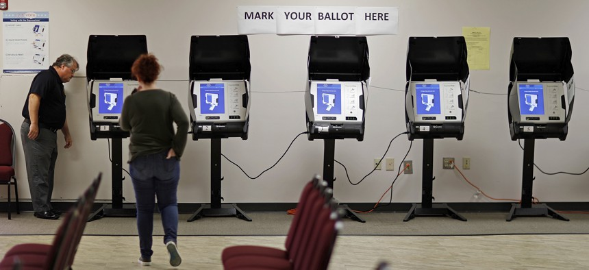 In this Oct. 19, 2017, file photo, Kelly Monroe, investigator with the Georgia secretary of state office, left, takes a look at a new voting machine being tested at a polling site in Conyers, Ga.