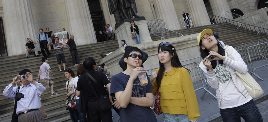 A group of tourists from China take in the sights of the New York Stock Exchange and Federal Hall National Memorial, in New York.