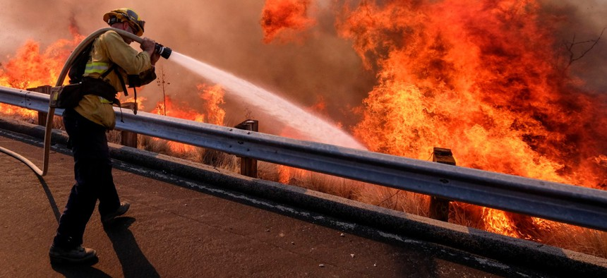 In this Nov. 12, 2018 file photo a firefighter battles a fire along the Ronald Reagan Freeway, aka state Highway 118, in Simi Valley, Calif.