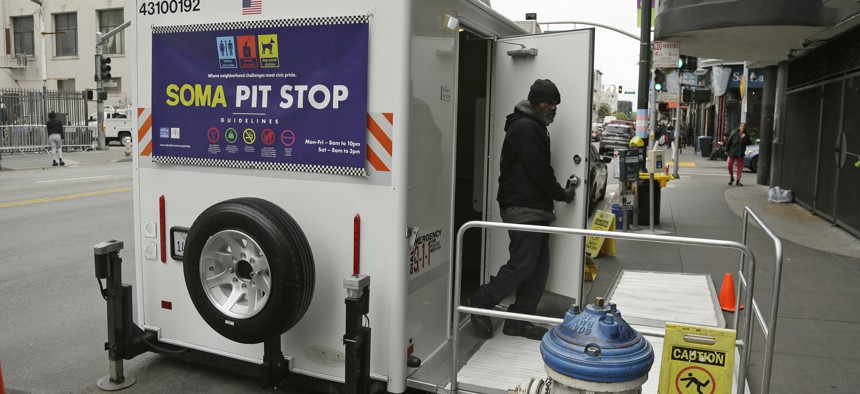 """An attendant exits a """"Pit Stop"""" public toilet on Sixth Street in San Francisco."""