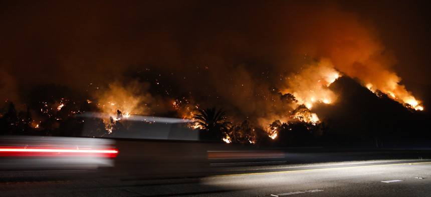 Traffic moves along the Highway 33 in Oak View, Calif. as a wildfires burned in 2017. The wildfires northwest of Los Angeles caused tens of thousands of people to evacuate.