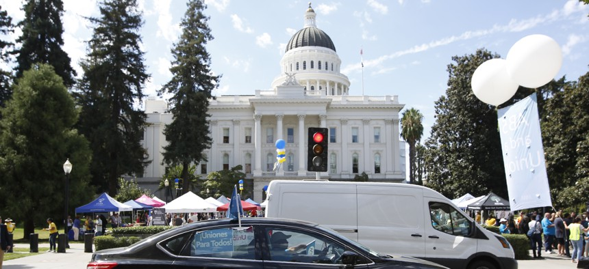 Dozens of supporters of a measure to limit when companies can label workers as independent contractors circle the Capitol during a rally in Sacramento, Calif., on Aug. 28, 2019.