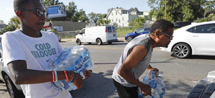 Volunteer Matthew Tiggs, left, helps Newark resident Mack Mayton load cases of bottled water into the trunk of his car, Aug. 12, 2019, in Newark, N.J., after Mayotn picked it up at the Boylan Street Recreation Center.